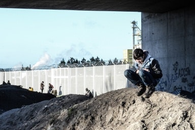 A boy squatting on a dirt pile near a tall fence