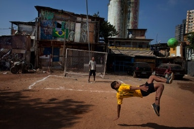 Two boys playing football in a dirt lot