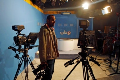 A man stands in a television studio holding a camera