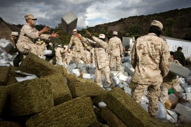 Soldiers gathering bales of marijuana