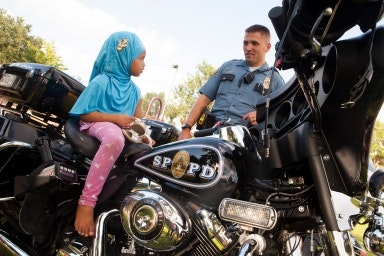 A girl sits on a police motocycle