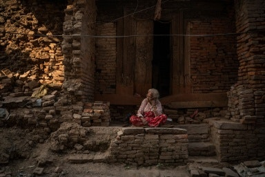 A woman sitting surrounded by bricks