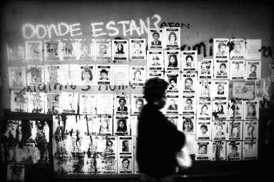 A person walks past a wall pasted with posters
