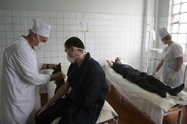 Two men on hospital beds wearing face masks