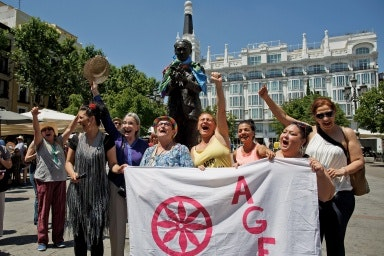 A group of women celebrating and holding a banner