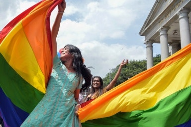 People dancing with rainbow flag
