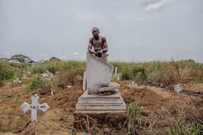 A man leaning on a tombstone
