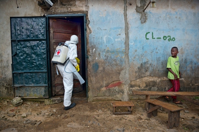 Worker entering a home with disinfection equipment