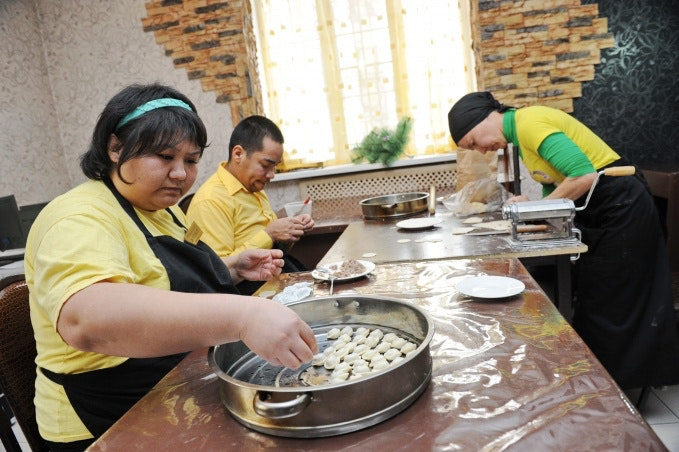 People making dumplings at a large table