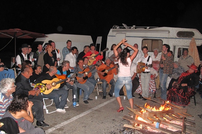 A group of people playing musical instrument and a woman dancing