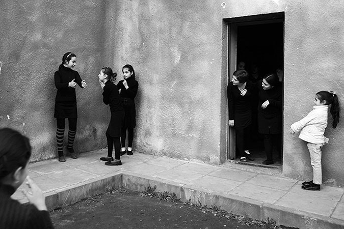 Girls playing outside a building.