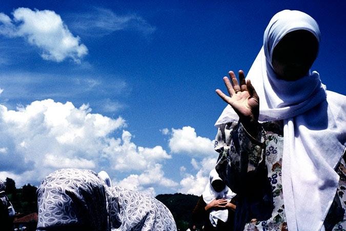 A muslim widow praying at a memorial.