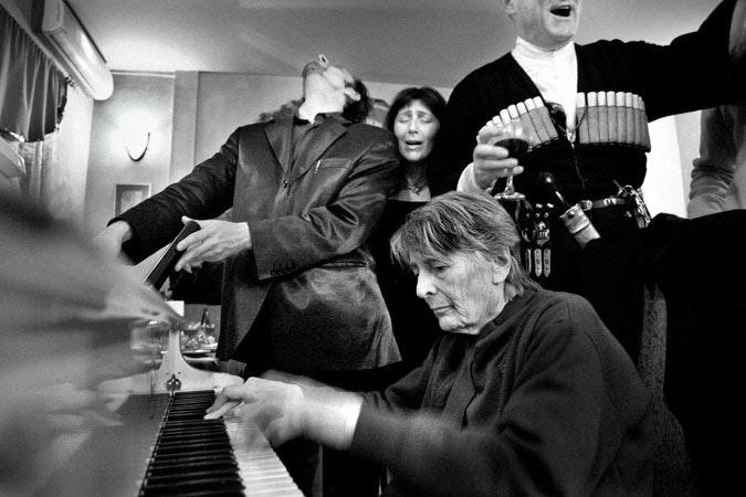 People gather around piano