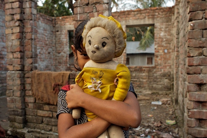 Young girl holding doll.