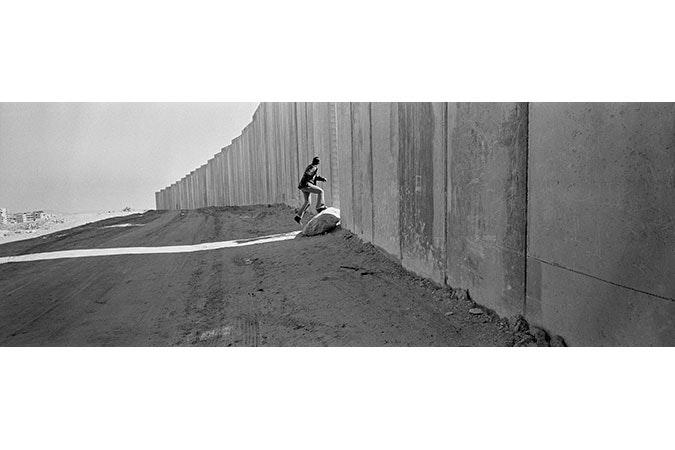 Man running through break in wall.