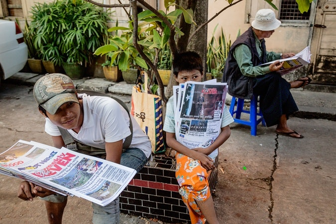 Boys sitting with newspapers