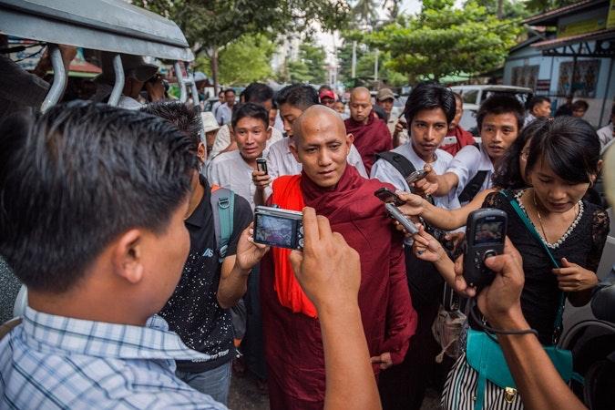 A monk walks through crowd