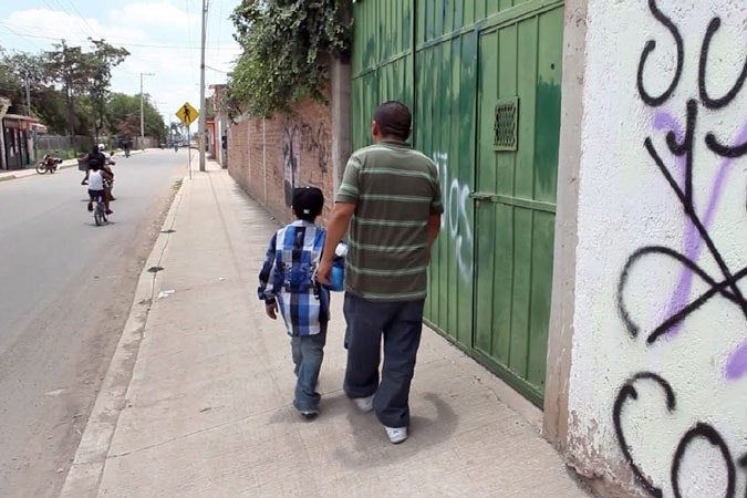 Father and son walking down a street