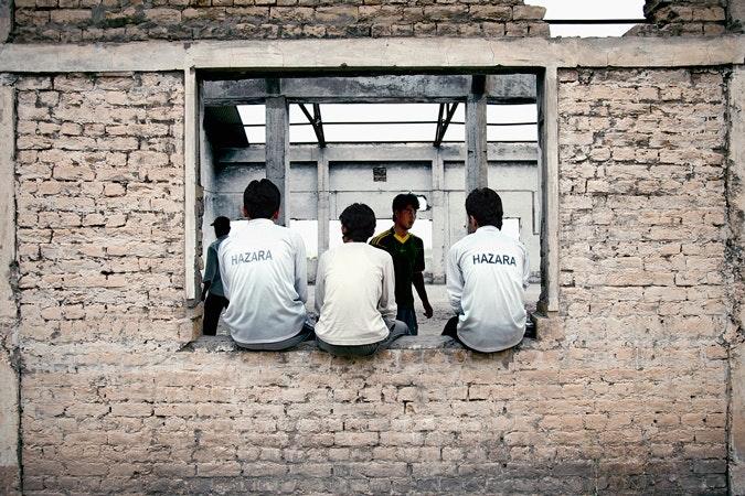 Three boys sitting on a window sill