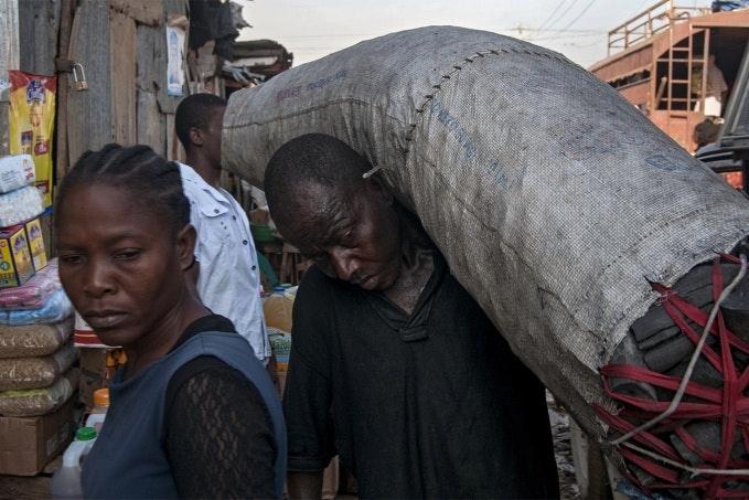 Man carries bag of coal