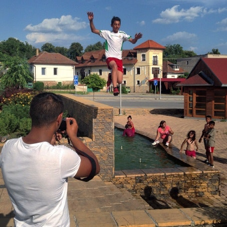 A boy jumping and a man filming