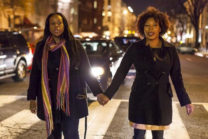 Women hold hands outside