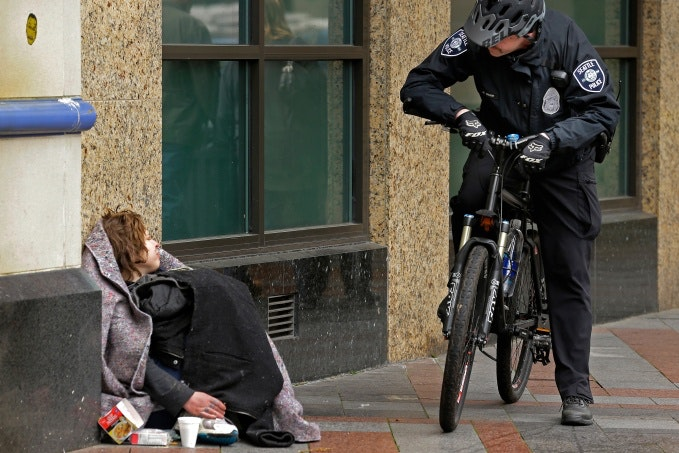 Police officer talking to a woman wrapped in a blanket