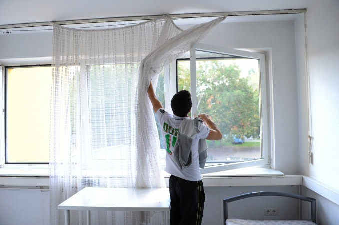 A young man opening a window
