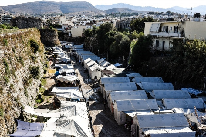 A row of refugee agency tents next to a fortress wall