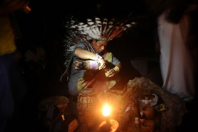 A man pouring a drink by candlelight