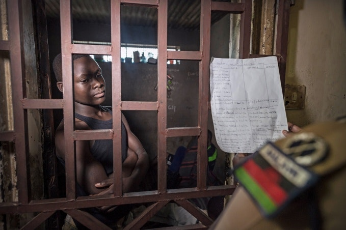 A young man in a jail cell