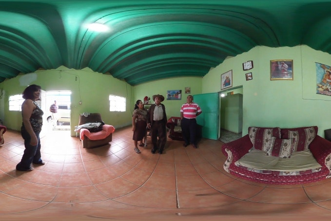 A distorted 360 degree video still of a family in a green room