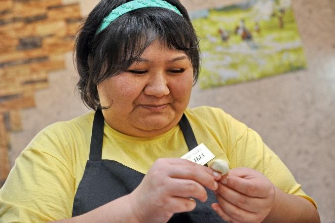 A woman forming a dumpling