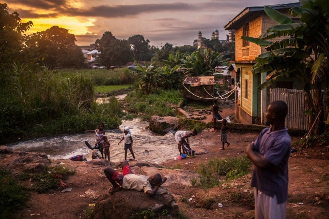 People along a river at sunset