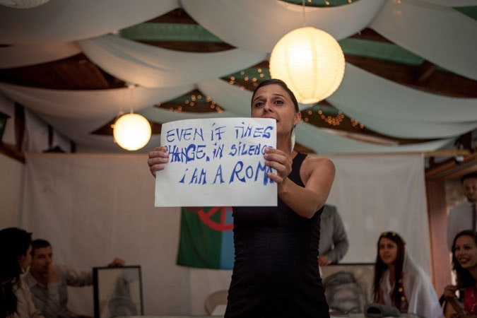 """Woman holding a sign that reads, """"Even if times change, in silence I am a Roma."""""""