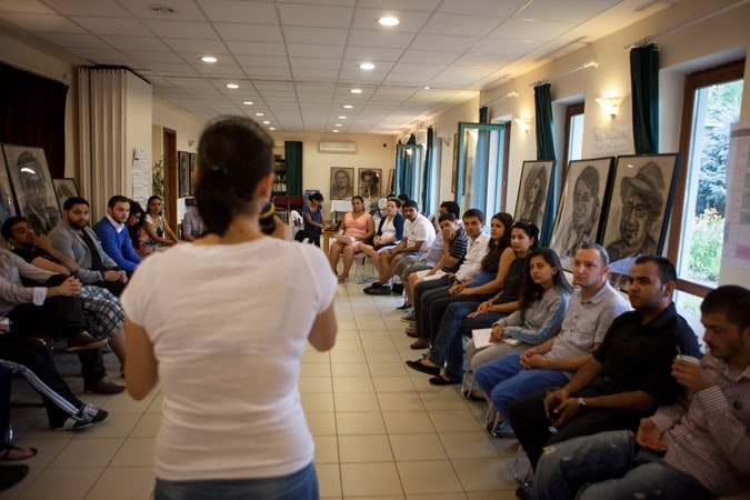 Woman holding microphone, speaking to a group of Barvalipe participants.