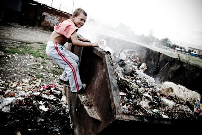 A boy plays in a dumpster in the Roma settlement near the Kosovo city of Gjakova.