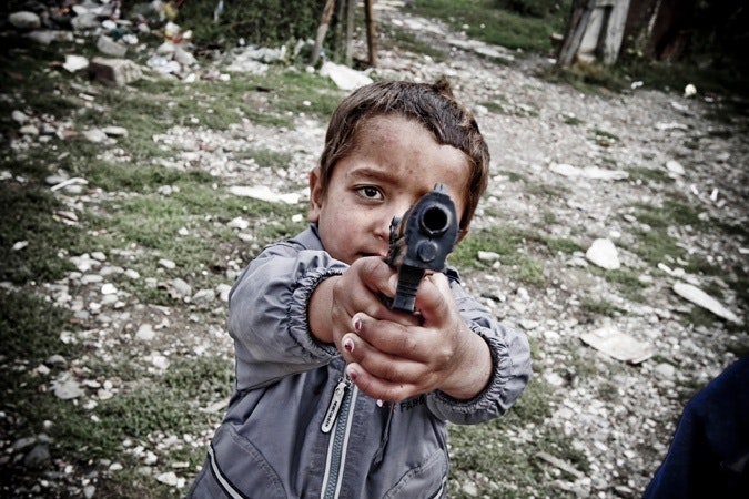 A boy plays with a toy gun