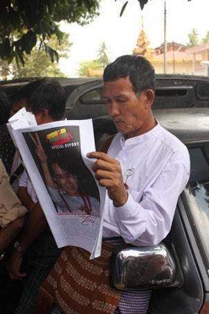 Man reading newspaper with Daw Aung San Suu Kyi on cover