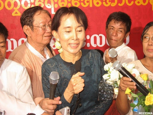 Daw Aung San Suu Kyi at press conference surrounded by reporters holding microphones