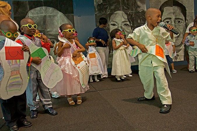 Kids wearing paper guitars and singing.