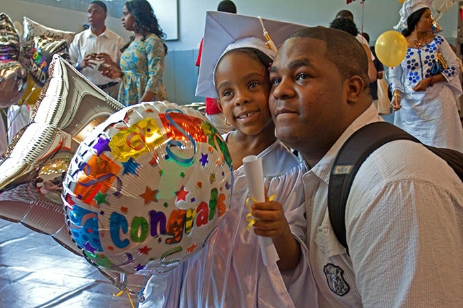 Young girl wearing cap and gown, and standing next to her father.