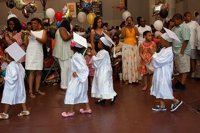 Children wearing cap and gowns.