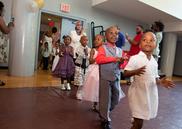 Children dressed up and walking into a gym.