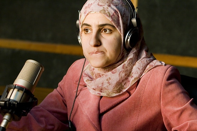 Women wearing headphones and sitting at microphone
