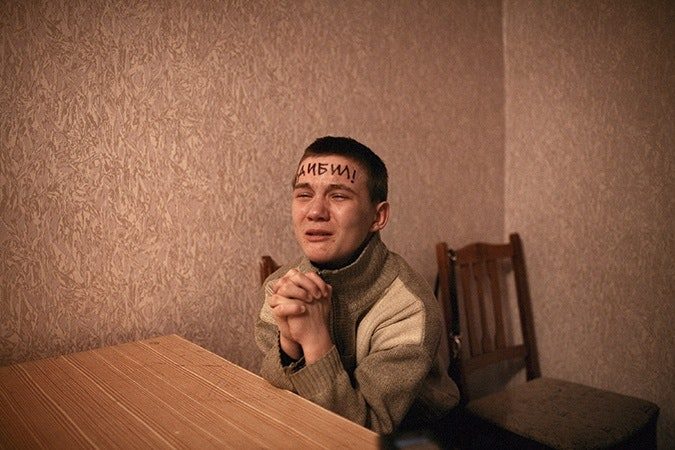 A young man with writing on his forehead