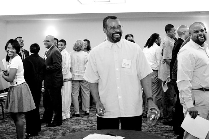 Estrus Tucker laughing among group of people
