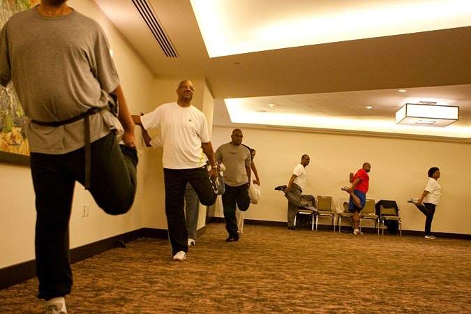 People stretching legs, doing qi-gong in a room