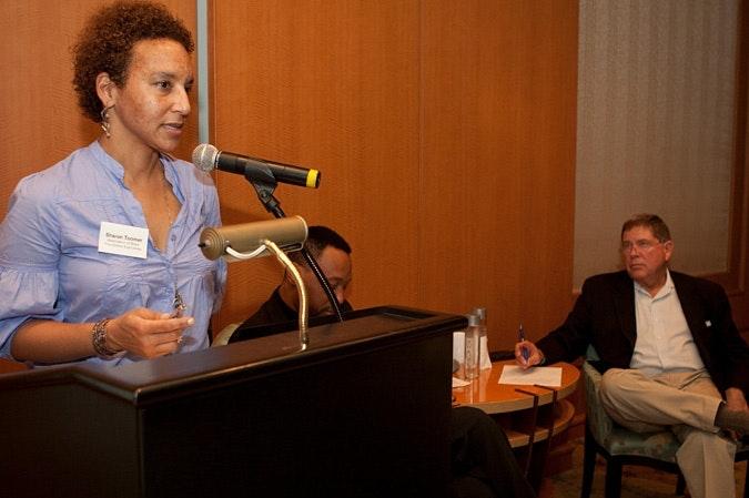 Sharon Toomer speaks into microphone at podium