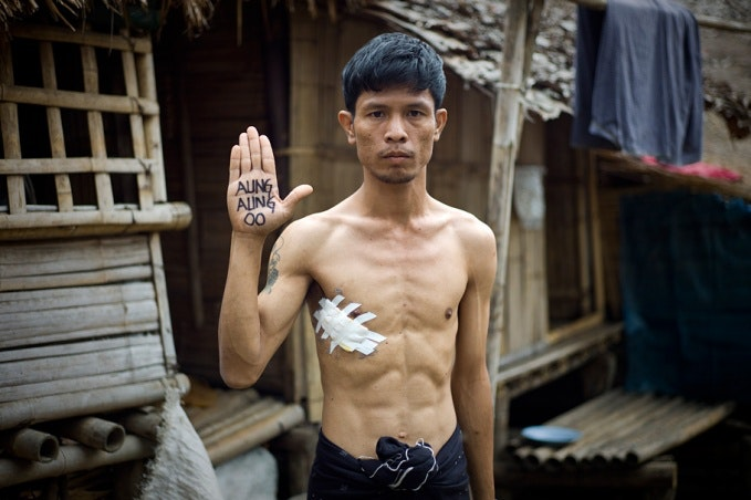 Tun Lin Kyaw raising his hand with writing on it